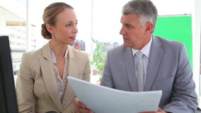 Two colleagues talking while reading a document. In an office stock footage