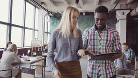 Two colleagues walking through the modern office and talking. African man and caucasian woman discussing the documents. Small start-up multiethnic company stock footage