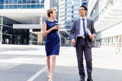 Two colleagues walking together in a city Stock Images