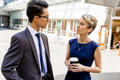 Two colleagues walking together in a city Stock Photos