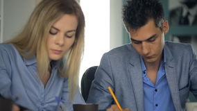 Two colleagues work in office sitting at table. stock footage