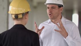 Two colleagues in the work plan discussing at a construction site. Close up. Professional shot in 4K resolution. 104. You can use it e.g. in your commercial stock video