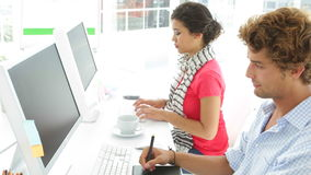 Two colleagues working next to each other. In creative office stock footage