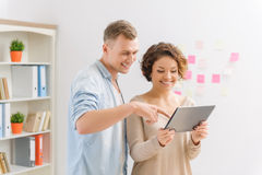 Two colleagues are working with portable tablet Stock Photos