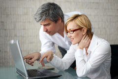 Two colleagues working together in business environment Stock Photos