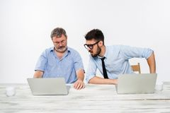 The two colleagues working together at office on white background Stock Photos