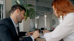 Two colleagues are working together on the project in the office: man in suit making notes. And woman with red hair talking to him. Indoors stock video