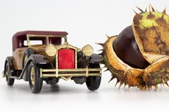 Horse-chestnut conker and oldtimer toy car royalty free stock image