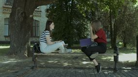 Two college girls talking on the bench after study. Two attractive female college friends with textbooks talking after study while sitting on the bench in park stock video