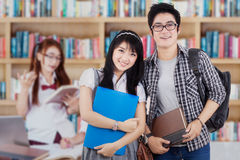 Two college student with group in library Stock Images