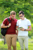 Two college students discussing a subject while walking at colle Stock Images