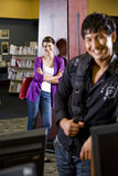 Two college students hanging out in library. Two university students hanging out in school library, focus on attractive female student in background Stock Photo