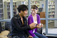 Two college students with music players in library. Two university students looking at music players in school library stock image