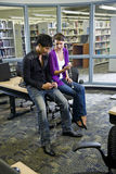 Two college students with music players in library. Two university students looking at music players in school library royalty free stock photos