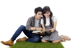 Two college students reading book on grass. Two attractive young couple of college students reading a book together while sitting on the grass, isolated on white Stock Images