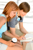 Two college students reading book while sitting. Boy and girl studying Stock Photo