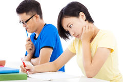 Two college students sitting an exam in a classroom Stock Photos