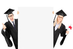 Two college students standing behind blank panel and gesturing s. Uccess isolated on white background Royalty Free Stock Photography