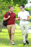 Two college students  studying together while walking and lookin Royalty Free Stock Images