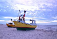 Two color boats an sea coast with blue sky. And sand. Sunset in summer Stock Photo