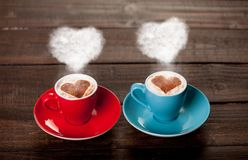 Two color cups of coffee with heart shape steams. On wooden table Royalty Free Stock Images