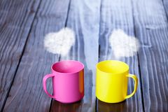 Two color cups of coffee with heart shape steams. On wooden table Royalty Free Stock Photo