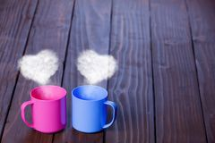 Two color cups of coffee with heart shape steams. On wooden table Stock Photography