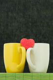 Two color cups and heart Stock Photos