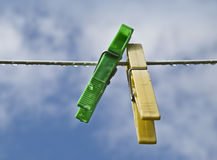 Two color pegs in a cloth line. Yellow and green pegs hanging on a cloth wire Royalty Free Stock Photography