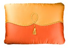 Two-color sofa cushion decorated with a cord, a bead and a brush Royalty Free Stock Photography