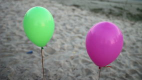 Two colored balloons. Colored balloons on sandy beach stock video footage