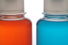 Two colored bottles. Part over white Royalty Free Stock Photo