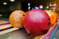 Two colored bowling balls of number 14 and 13 Royalty Free Stock Photography