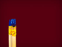Two colored brushes with smile hold a hearth and kissing. Stock Photo