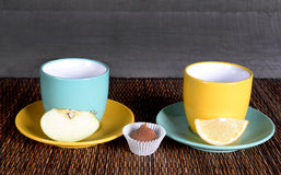 Two colored cups and mugs on a wooden background with fruits Stock Photos