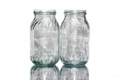 Two colored empty jars. Two empty colored jars on white background having light reflection on them stock photos