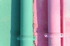 Two colored gutters on the painted wall of the house. In Burano Island near Venice Italy Stock Image