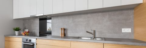 Kitchen with concrete worktop. Two colored kitchen furniture with concrete worktop and steel appliances, panorama Stock Photos