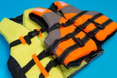 Two colored life jackets on a blue background, concept of saving life in water. Close-up stock photos