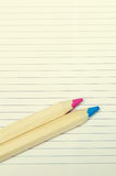 Two colored pink and blue wooden pencils on white paper Royalty Free Stock Photos