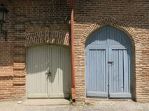 Two colored wooden exterior doors royalty free stock image