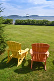 Two colorful adirondack chairs face the harbor Royalty Free Stock Photo