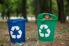 Two colorful boxes. Sitting boy have fun inside recyling waste bin outside. Concept of environmental protection. stock image