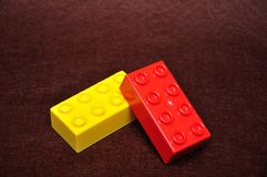 Two colorful building blocks. Isolated on a brown background stock images