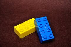 Two colorful building blocks. Isolated on a brown background stock photography