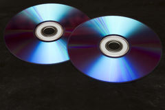 Two colorful CDs on a black background. Two colorful CDs on uneven leather black background Royalty Free Stock Images