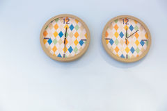 Two colorful clocks. On light blue wall stock photo