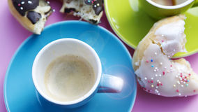 Two colorful cups of coffee and donuts royalty free stock photo