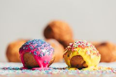 Two decorated doughnuts laying on a table. Two colorful decorated doughnuts laying on a table. Homemade bakings Stock Photo