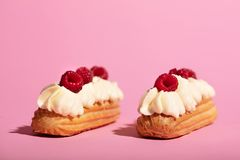 Two colorful eclairs laying on pink background. royalty free stock images